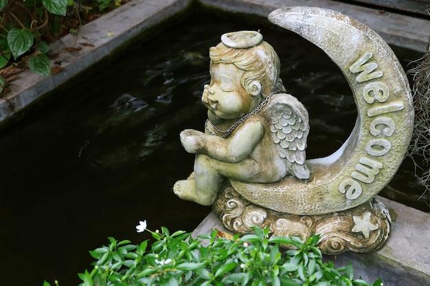 Entzückender engel, der auf einer halbmondwillkommensskulptur an der gartenteichseite sitzt