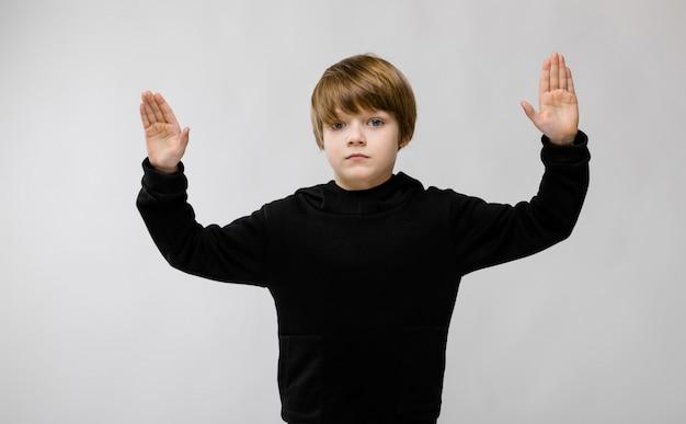Entzückender ernster kleiner junge, der mit den händen oben steht