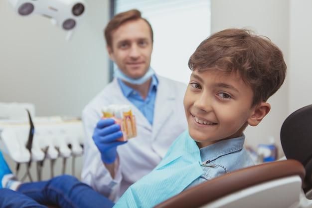 Entzückender glücklicher junge, der zur kamera lächelt, während er in einem zahnarztstuhl sitzt