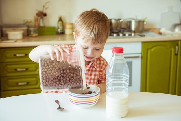 Entzückender glücklicher kinderjunge, der frühstücks- oder mittagessenschokoladenmüsli mit milch vorbereitet