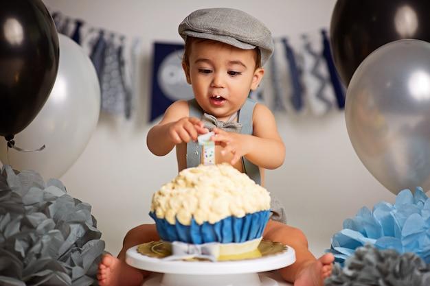 Entzückender glücklicher kleiner junge mit einem kuchen, um einen geburtstag zu feiern