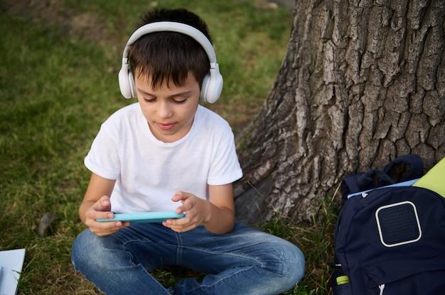 Entzückender gutaussehender schüler im grundschulalter mit drahtlosen kopfhörern, der sich darauf konzentriert, mit dem smartphone zu spielen, auf dem grünen gras des stadtparks ruht, schulsachen neben ihm liegen