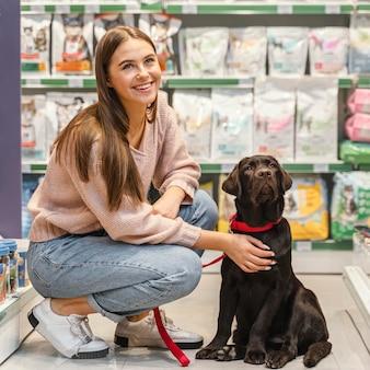 Entzückender hund mit besitzerin in der tierhandlung
