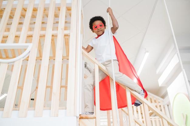 Entzückender junge der afrikanischen ethnischen zugehörigkeit, der roten mantel des übermenschen trägt, der durch seil hält, während geländer hinuntergleiten