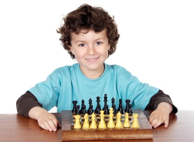 Entzückender junge, der das schach über weißem hintergrund spielt
