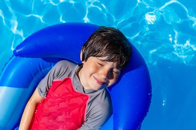 Entzückender junge, der im schwimmbad auf einer aufblasbaren matratze ruht