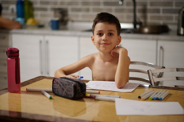 Entzückender junge, der in die kamera schaut, während er am tisch sitzt und zu hause bilder zeichnet