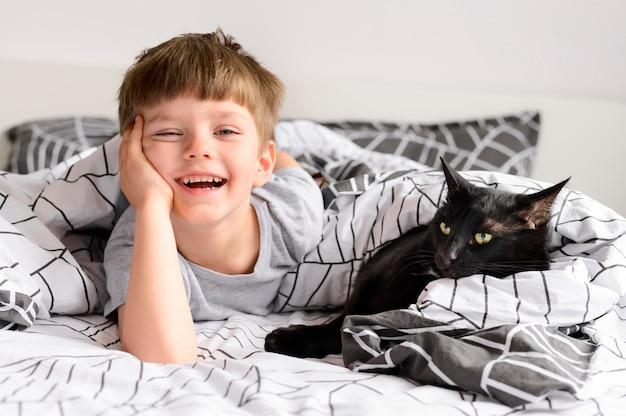 Entzückender junge, der mit seiner katze aufwirft