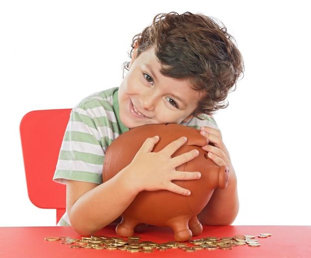 Entzückender junge, der seine einsparungen in ihren geldkasten einsetzt