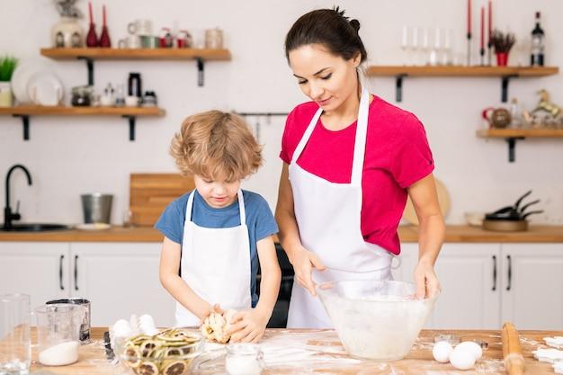 Entzückender junge, der selbst gemachten teig für kekse knetet, während er seiner mutter beim kochen am küchentisch hilft