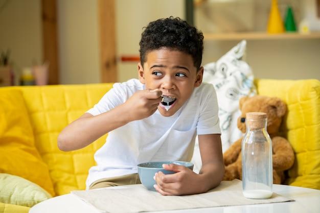 Entzückender junge des grundschulalters in der freizeitkleidung, die auf dem boden innerhalb des weißen zeltes sitzt und mit dem hölzernen spielzeugzug im kindergarten spielt