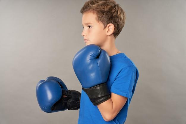 Entzückender junge in boxhandschuhen, der vor grauem hintergrund steht