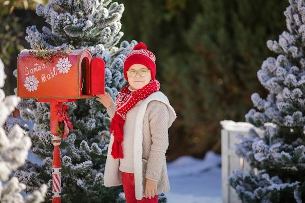 Entzückender junge mit den gläsern, die ihren brief an sankt, weihnachtszeit senden
