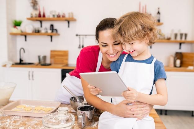 Entzückender junge mit touchpad und seiner glücklichen mutter, die videorezept bespricht, während sie wählt, was zum abendessen gekocht werden soll