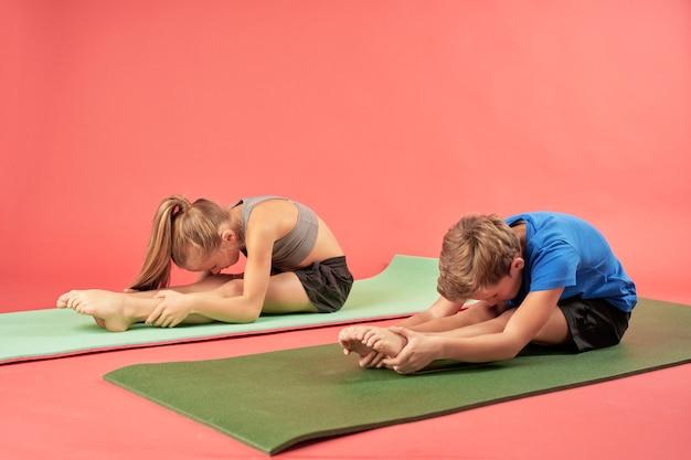 Entzückender junge und mädchen, die yoga vor rotem hintergrund praktizieren