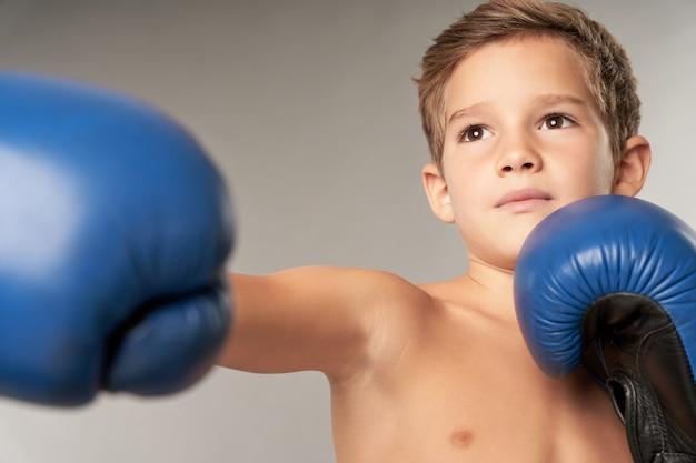 Entzückender jungenboxer, der boxschläge im studio übt