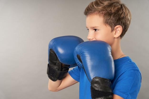 Entzückender jungenboxer, der sportboxhandschuhe und blaues hemd trägt, während er die kampfhaltung macht