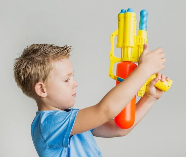 Entzückender junger junge, der mit wasserwerfer spielt