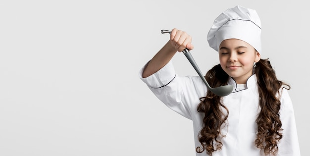 Entzückender junger koch, der suppenkelle hält