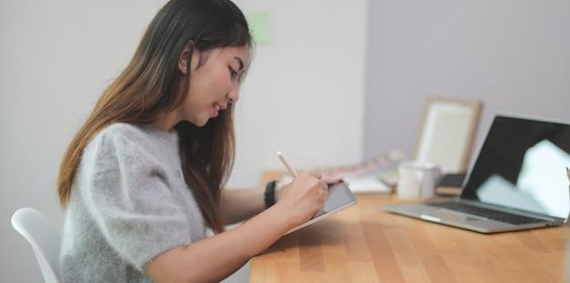 Entzückender junger weiblicher freiberufler, der ihr ideenkonzept auf tablette schreibt