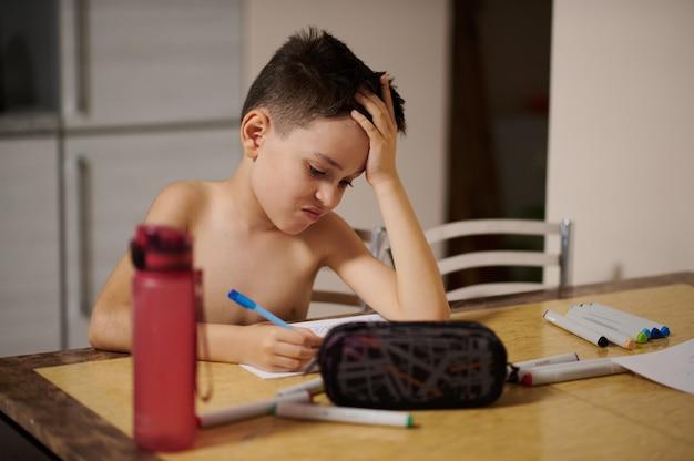 Entzückender kinderjunge, der am tisch sitzt und sich auf das zeichnen von comics konzentriert. federmäppchen im vordergrund