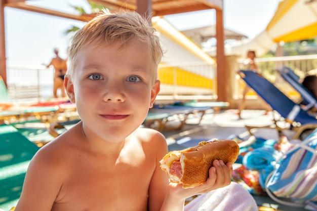 Entzückender kinderjunge, der hot dog am strandaquapark isst