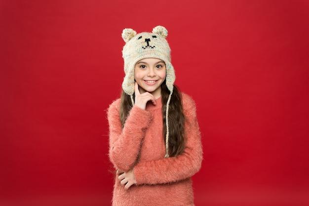 Entzückender kleiner bär. winter-outfit. kleines kind trägt strickmütze. warm bleiben. kleines mädchen wintermode-accessoire. kleines kind lange haare tragen hut roten hintergrund. nettes modell genießen winterstil.