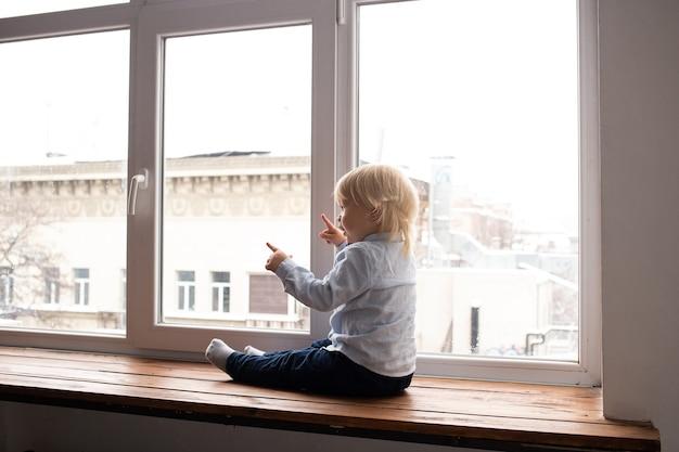 Entzückender kleiner blonder junge, der auf der fensterbank sitzt. ein kind schaut aus dem fenster.