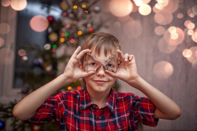 Entzückender kleiner junge bereitet den lebkuchen zu, backt plätzchen in der weihnachtsküche.