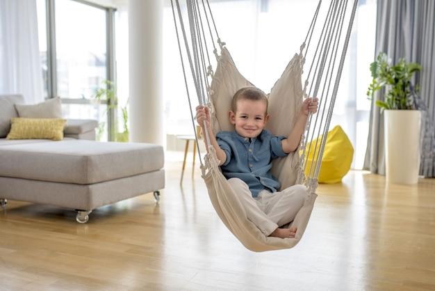 Entzückender kleiner junge, der auf der hängematte im haus sitzt