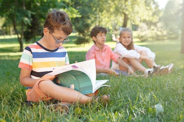 Entzückender kleiner junge, der ein buch liest und mit seinen freunden im park im gras sitzt