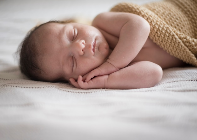 Entzückender kleiner junge, der ein schläfchen hält