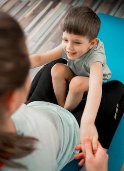 Entzückender kleiner junge, der glücklich ist, mit mutter zu trainieren