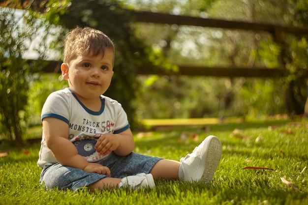 Entzückender kleiner junge, der im frühjahr mitten auf einem grünen rasen sitzt.