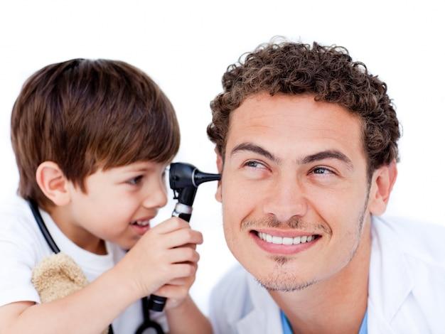 Entzückender kleiner junge, der mit dem doktor spielt