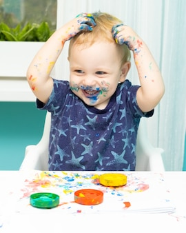 Entzückender kleiner junge, der mit fingerfarben malt