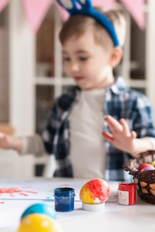 Entzückender kleiner junge, der mit ostereiern spielt