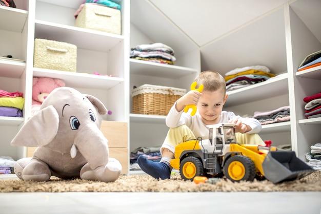 Entzückender kleiner junge, der mit spielzeug spielt, während er in seinem spielzimmer auf dem boden sitzt