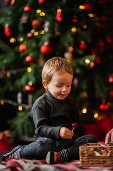 Entzückender kleiner junge, der mit weihnachtsspielzeug spielt