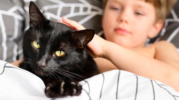 Entzückender kleiner junge, der seine katze streichelt