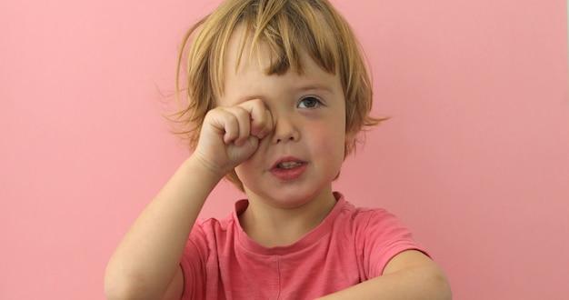 Entzückender kleiner junge im rosa t-shirt, welches das auge schaut schläfrig reibt