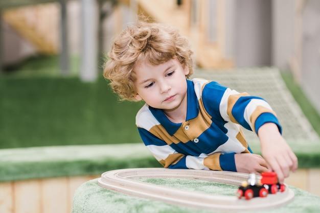 Entzückender kleiner junge in der freizeitkleidung, die auf dem boden des spielplatzes beim spielen von spielzeugeisenbahnen im kindergarten oder im freizeitzentrum liegt
