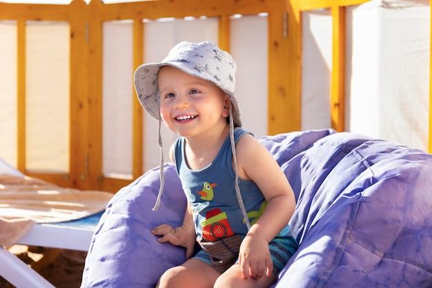 Entzückender kleiner junge in panama sitzt auf dem müllsackstuhl am strand.