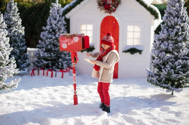 Entzückender kleiner junge mit dem roten hut und grünen gläsern, die ihren brief an sankt, weihnachtszeit senden