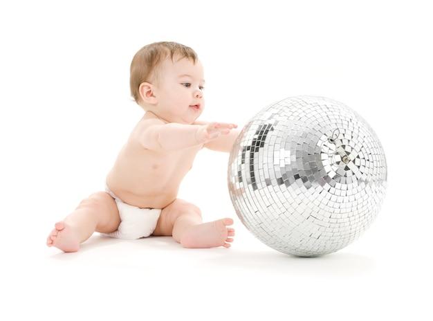 Entzückender kleiner junge mit großer discokugel über weiß
