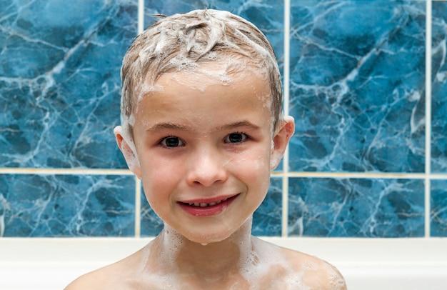 Entzückender kleiner junge mit shampoo-seifenlauge auf haar, das bad nimmt. nahaufnahmeporträt des lächelnden kindes, des gesundheits- und hygienekonzepts als logo. isoliert auf weißem und blauem hintergrund mit beschneidungspfad.