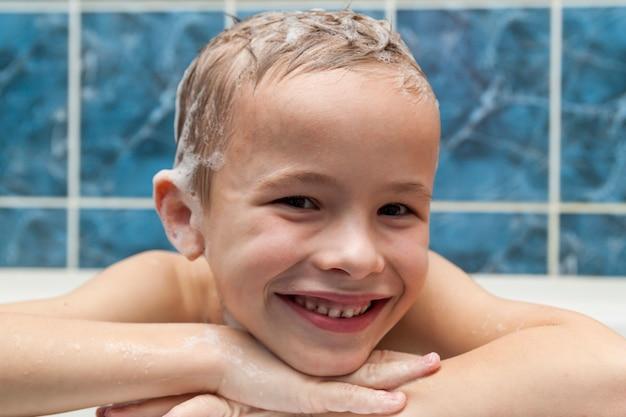 Entzückender kleiner junge mit shampoo-seifenlauge auf haar, das bad nimmt. nahaufnahmeporträt des lächelnden kindes, des gesundheits- und hygienekonzepts als logo.