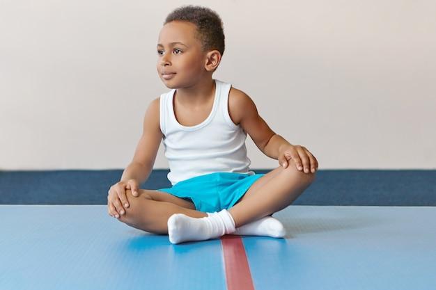 Entzückender kleiner sportler des afrikanischen aussehens, der auf matte mit gekreuzten beinen sitzt und sich nach intensivem training entspannt.