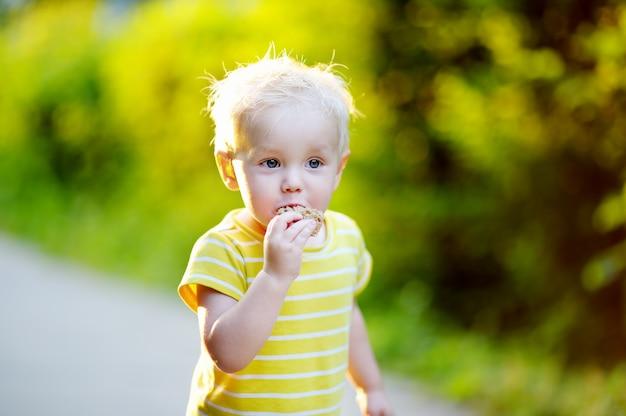 Entzückender kleinkindjunge, der draußen stück brot isst