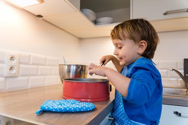 Entzückender kleinkindjunge, der küchenschürze trägt, die allein apfelkuchen backt